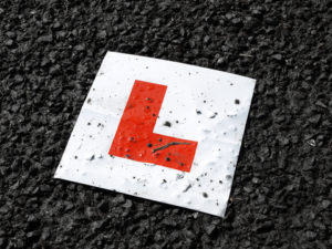 Learner drive red L plate against black tarmac. Referring to public speaking for beginners: practice, belief and ability